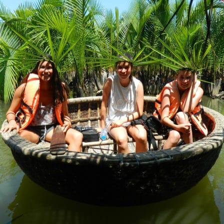 Mennesker i rund båd på flod i Hoi An
