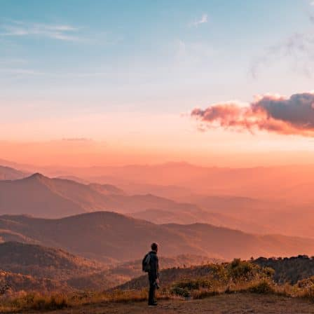 mand står på bakke med bjergudsigt og solnedgang