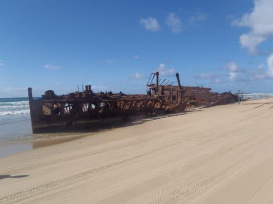 Rester af skib på strand ved vandkanten