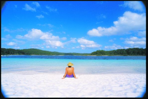Kvinder sidder på kridhvid strand med turkisblåt vand