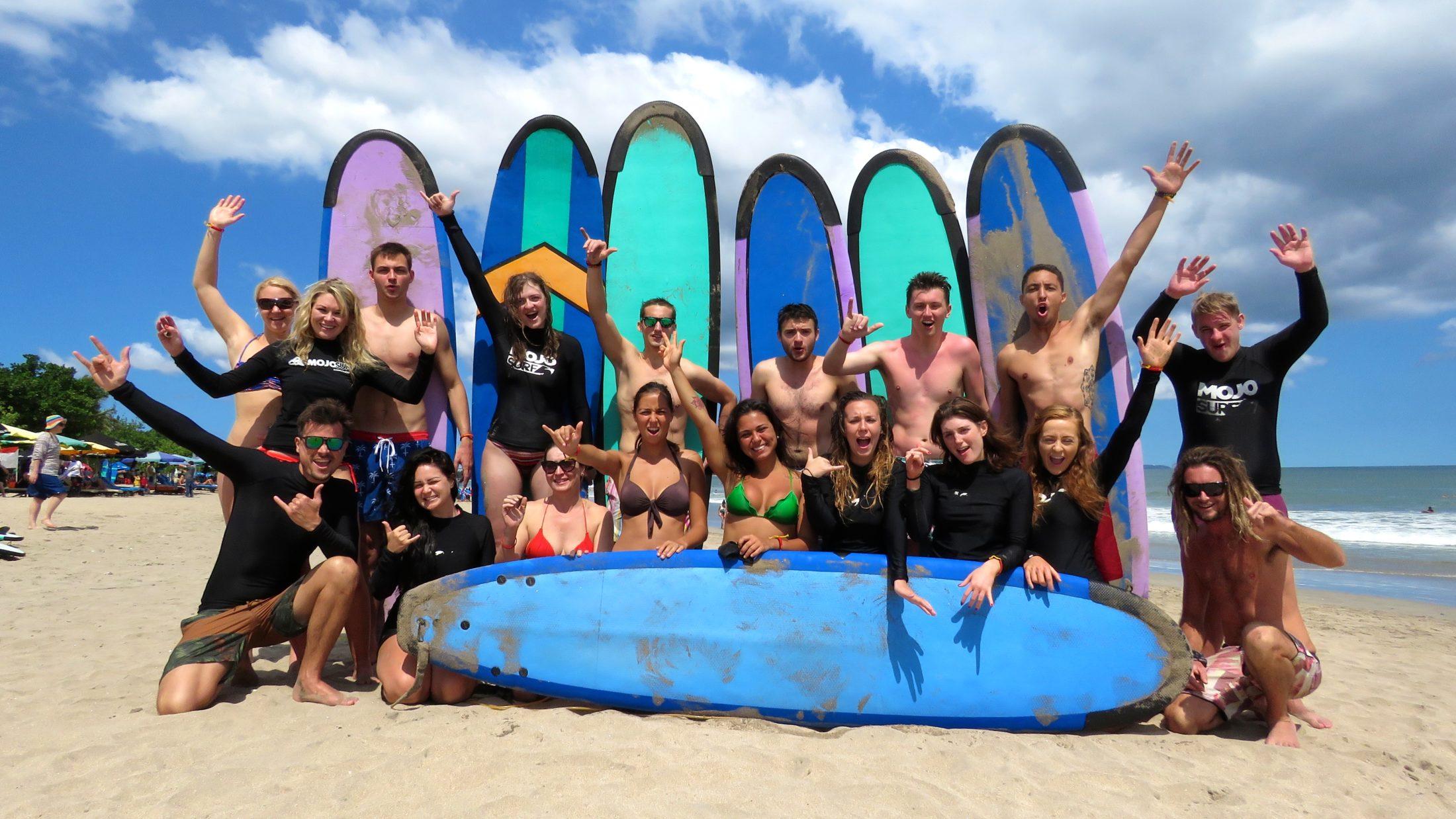 Gruppebillede af surfere på stranden