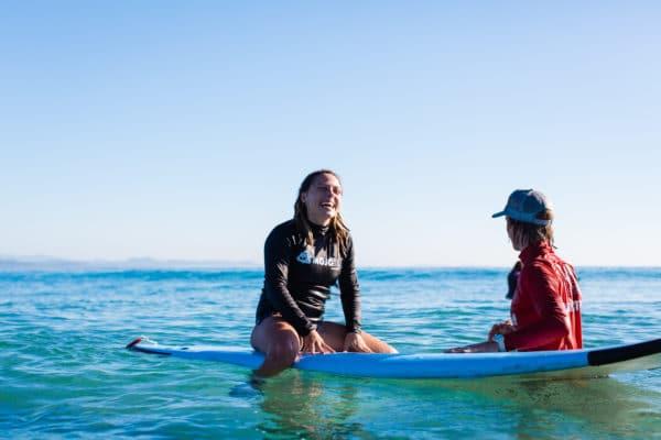 Kvinde på surfbræt med instruktør i vandet
