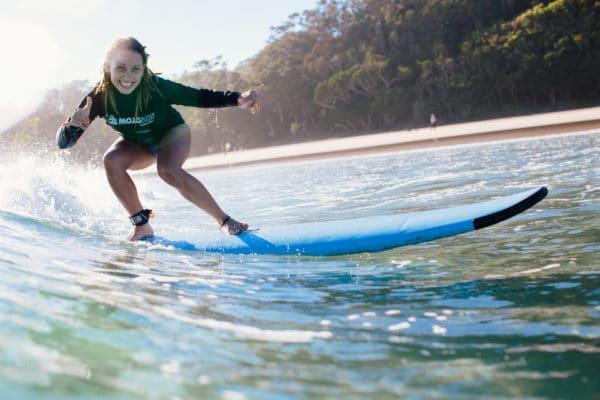 Kvindelig surfer på bølge med strand og træer i baggrunden