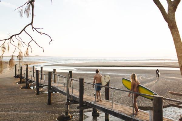 Mand og kvinde går med surfbræt over gangbro på stranden