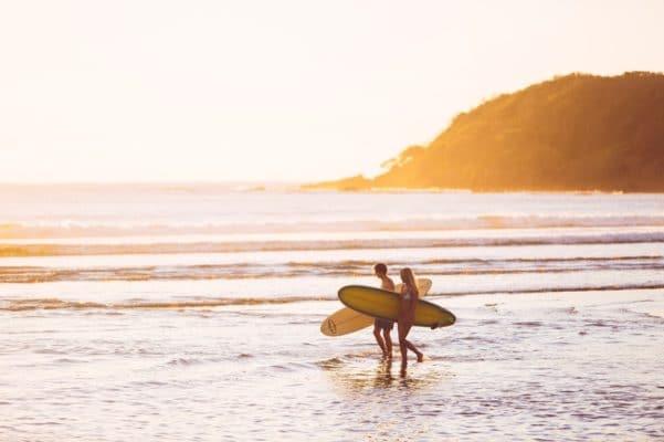 Kvinde om mand med surfbræt på stranden