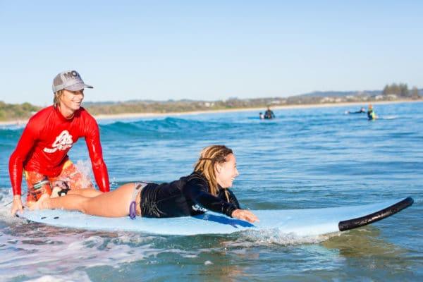 Kvinde lærer at surfe med instruktør