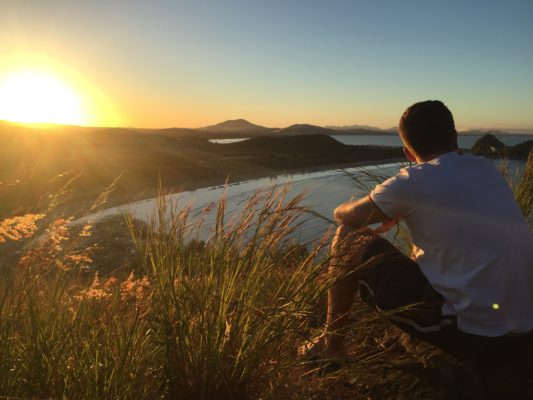 Mand sidder på eng med solnedgang