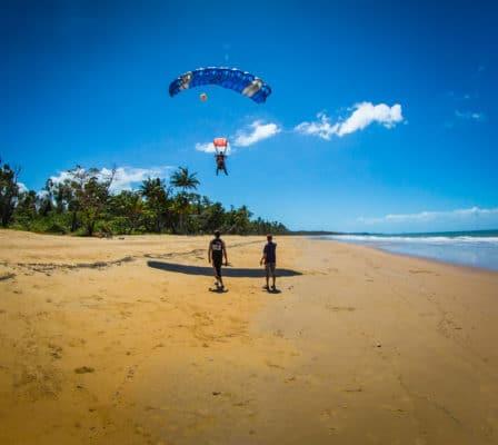 Landing på strand med faldskærm