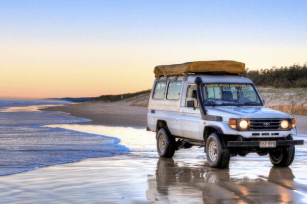 Bil på stranden i vandkanten