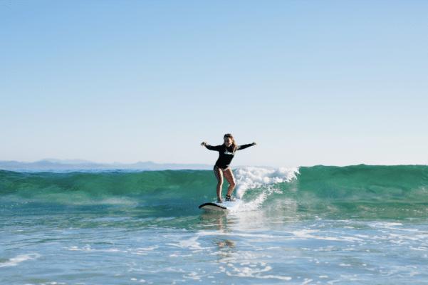 Kvinde surfer på bølge