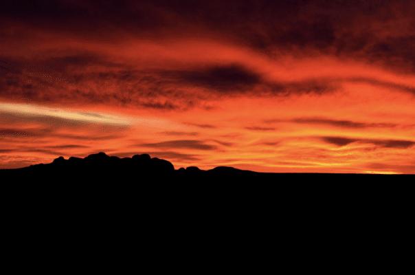 Mørklagt landskab med orange himmel