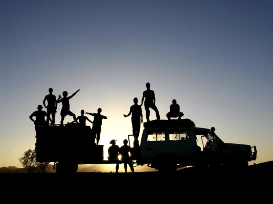 Silhouetter af folk på bil i solnedgang