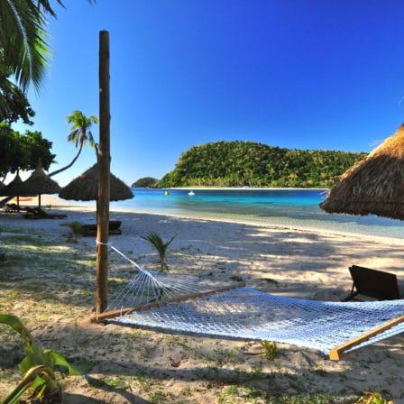 Strand med hængekøje, bambusparasoller og havudsigt