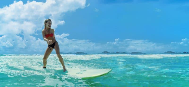 Kvinde står på surfbræt