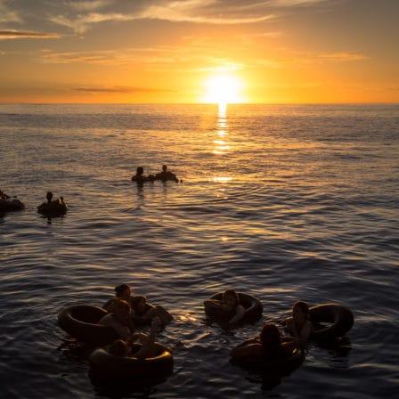 Sol går ned i vandet hvor mennesker bader