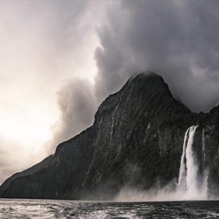 Overskyet mørk bjergkæde med vandfald