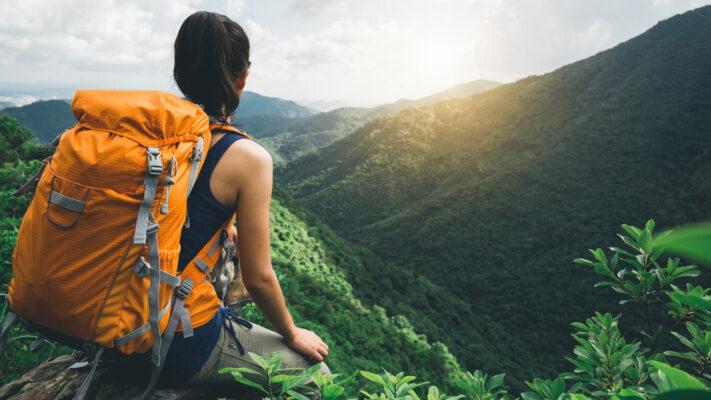Kvinde i bjergdal med solnedgang